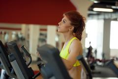 Pretty red-haired girl exercising on treadmill - stock photo
