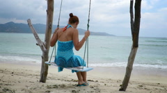 Woman in sarong gently swinging on a beach Stock Footage