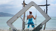 Woman on a swing in Gili Air island, Indonesia Stock Footage