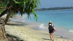 Girl walking down beautiful coastline with backpack and a hat Stock Footage