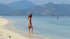 Girl in summer dress walking along beautiful beach Stock Footage