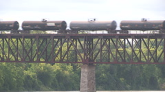 Train with crude oil and chemical tankers crosses bridge over pristine river Stock Footage