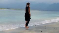 Woman in elegant black dress walking down beautiful beach - stock footage