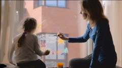 Young mother and her daughter paint on the window pane in children's room Stock Footage