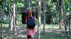 Girl with backpack walking on a path through tall palm trees in Ubud, Bali Stock Footage