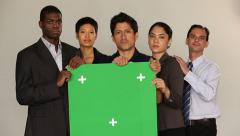 Multi ethnic group holding a green board. Serious, neutral mood. Stock Footage