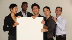 Multi ethnic group holding a white board. Smiling, casual mood. Stock Footage