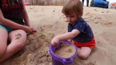 Mother and toddler playing on sandy river beach Stock Footage