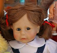 Old doll's face with long hair for sale in antiques shop Stock Photos