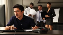 Frustrated male office worker at his desk. Colleagues chatting in backgound. Stock Footage