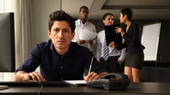 Frustrated male office worker. Colleagues chatting in background. Stock Footage