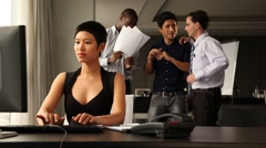 Asian female office staff working with colleague. Colleagues behaind chatting. Stock Footage