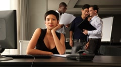 Asian female office worker fed up. Colleagues chatting and laughing in backgound Stock Footage