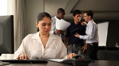 Female office staff working. Colleagues chatting and laughing in backgound. Stock Footage
