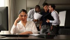 Female office worker fed up holding her head. Colleagues chatting in backgound. Stock Footage