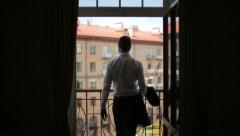 Silhouette of a man wears a jacket standing on the balcony of the hotel Stock Footage