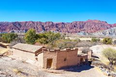 Stock Photo of rustic adobe building and red hills