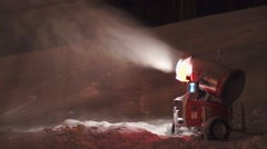 Snow cannon makes snow at ski resort mountain at night Stock Footage