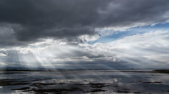 light beams through clouds over calm ocean,  Reykjavik, Iceland - stock footage