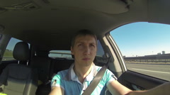Driving a car, inside front view af man driver sitting and looking forward Stock Footage