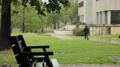 Man in Hoodie Walking on Sidewalk Stock Footage