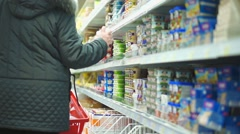 Customers selects milk products on shelves in supermarket Stock Footage