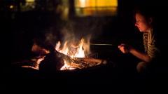 Woman bakes apple on bonfire Stock Footage