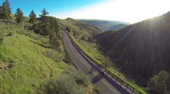 Aerial shot of man riding motorcycle on beautiful mountain road into sunrise. - stock footage