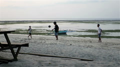 Kids kicking ball on beach by the sea Stock Footage