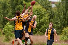 Players jump to catch ball in australian rules football game Stock Photos
