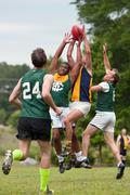 Players battle for ball in australian rules football game Stock Photos