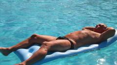 Male sunbathing on lilo Stock Footage