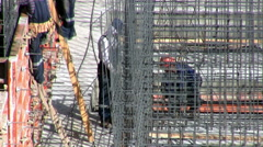 Workers on a construction site set reinforcement for concrete pouring - stock footage