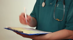 Doctor taking notes on clipboard, filling medical form, report - stock footage