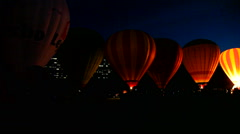 Hot Air Balloons light up the night in a night glow Stock Footage