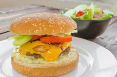 cheeseburger with bacon and tartar sauce and garden salad - stock photo