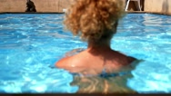 Stock Video Footage of Woman in Swimsuit Swimming in Blue Water Pool.