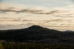 wispy, wavy clouds over mountain peak - stock photo