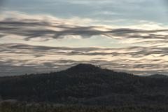 Wispy, wavy clouds over mountain peak Stock Photos
