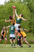 Men jump for ball in amateur australian rules football game Stock Photos