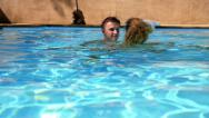 Stock Video Footage of Happy Smiling Couple Bathing Together in Pool. Slow Motion.