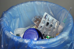 Disposing empty medication bottles, blister packs, used syringes, click for HD Stock Footage