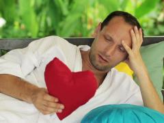 Sad man with heart-broken symbol on gazebo bed in garden NTSC Stock Footage