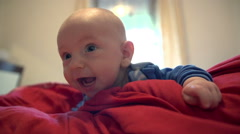 Infant is laying on the red blanket Stock Footage