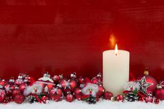 Red wooden christmas background with one burning advent candle. Stock Photos