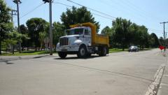 Dump truck driving down road, wide shot Stock Footage