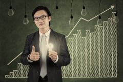 businessman holding lightbulb with upward graph - stock illustration