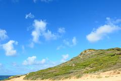 Stock Photo of green hill by the sea