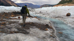 Climber Following Water Stream on Glacier HD Stock Footage