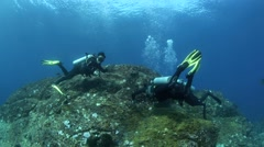 Scuba divers trying to hold onto reef during ascent safety stop Stock Footage